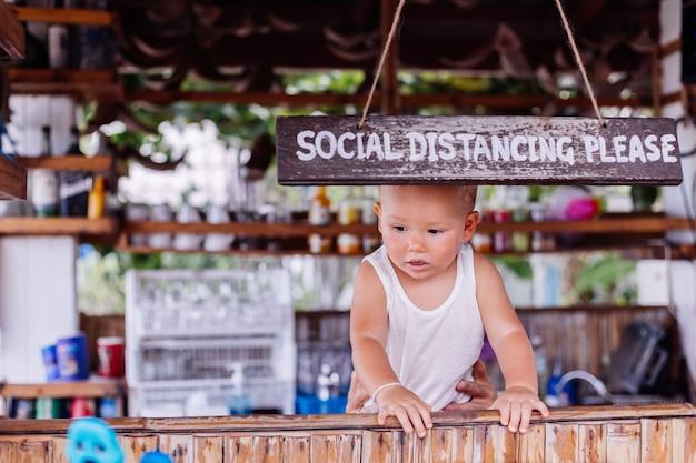 Menino de férias na tailândia com placa de distância social em bar