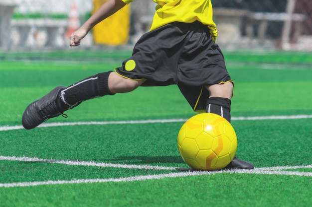 Menino de futebol está treinando chutando a bola no campo de treinamento de futebol