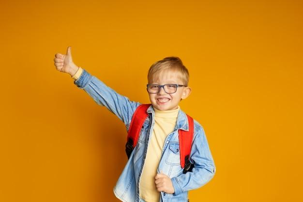 Menino de garoto garoto engraçado com livros sobre fundo amarelo