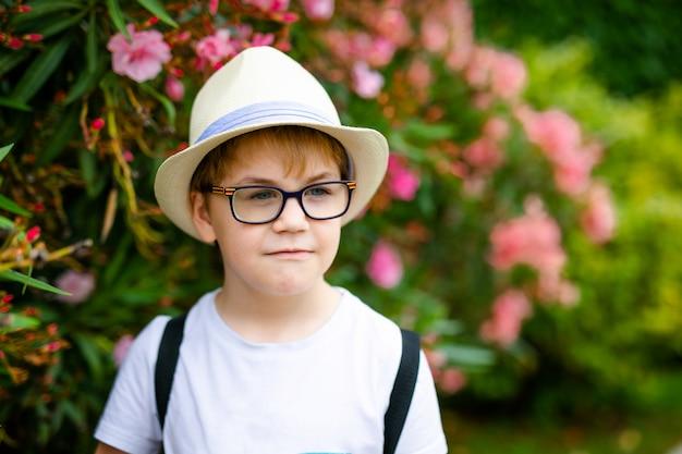 Menino de gengibre no chapéu de palha e óculos grandes perto do arbusto verde com flores cor de rosa no parque de verão