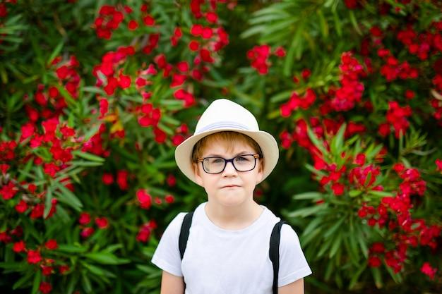 Menino de gengibre no chapéu de palha e óculos grandes perto do arbusto verde com flores vermelhas no parque de verão