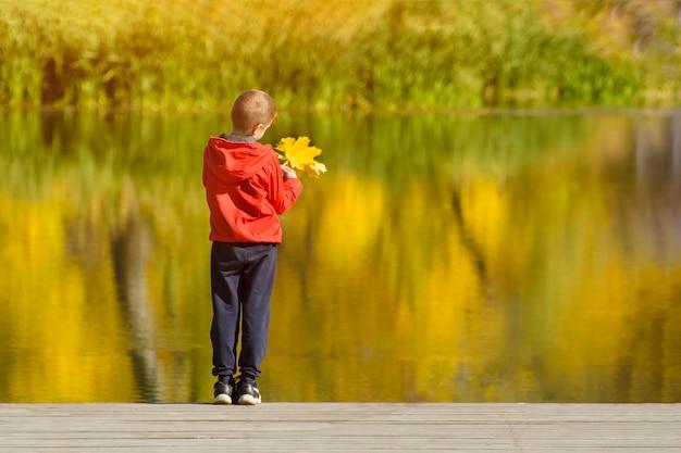 Menino de jaqueta vermelha em pé no cais com folhas na mão