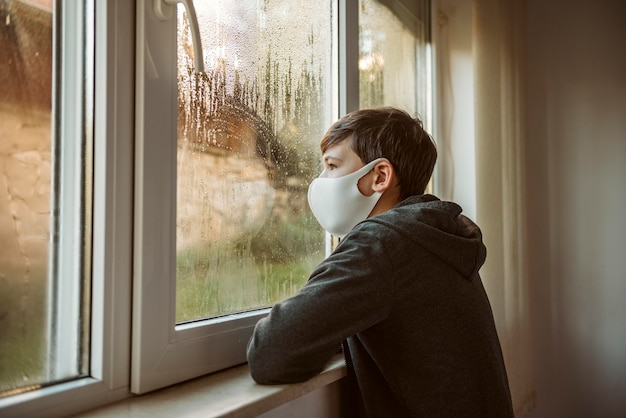 Menino de lado com máscara facial olhando pela janela