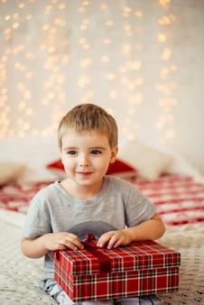 Menino de manhã de natal sentado na cama