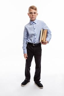 Menino de óculos com livros nas mãos. criança de 9 a 10 anos com camisa e calça azul. educação e estudo. altura toda. fundo branco. vertical.