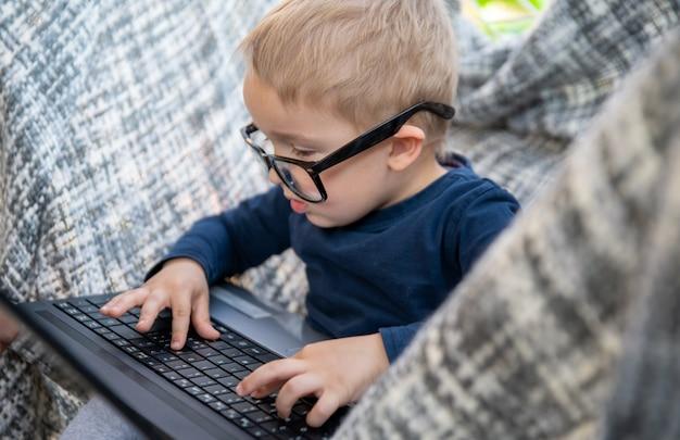 Menino de óculos do pai trabalha em um laptop no quintal em uma rede. trabalho inteligente, trabalho em casa