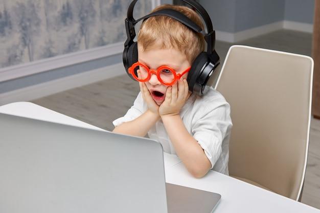Menino de óculos fica chocado e surpreso com o que viu na internet de um laptop