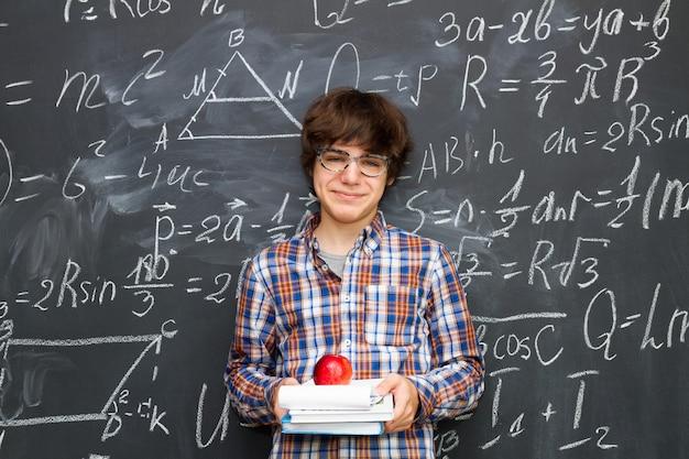 Menino de óculos segurando livros com maçã, quadro-negro cheio de fundo de fórmulas matemáticas