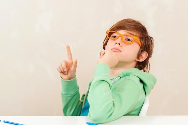 Menino de óculos sentado e pensando