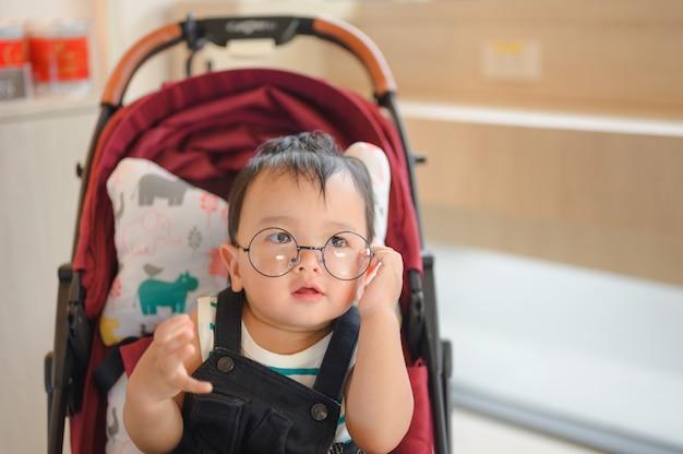 Menino de óculos sentado no carrinho moderno. viajar com crianças pequenas. transporte para família com criança.