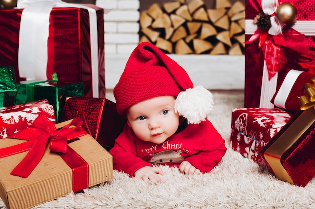 Menino de papai noel deitado no chão em casa decorada com presentes de natal