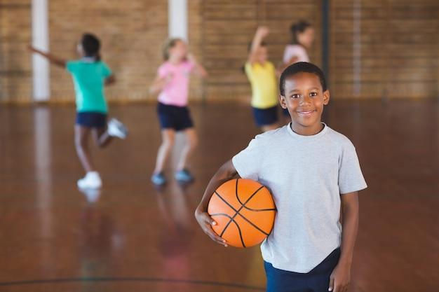 Menino de pé com bola na quadra de basquete