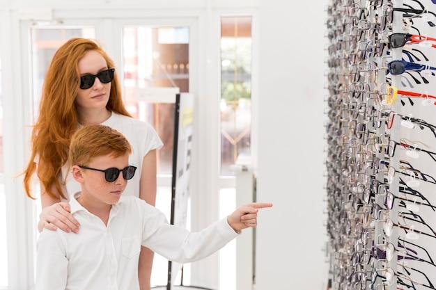 Menino de pé com sua irmã na loja de óptica e apontando para a cremalheira de óculos