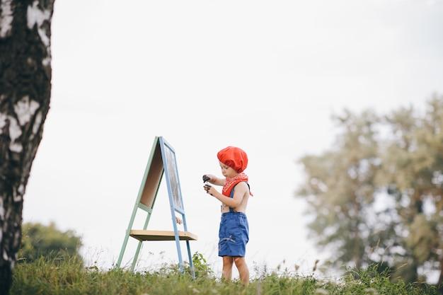 Menino de pé debaixo da árvore e desenhar o cavalete no parque