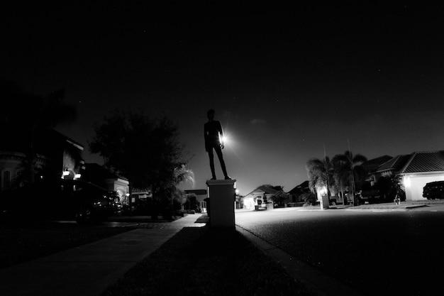 Menino de pé em uma caixa de correio à noite
