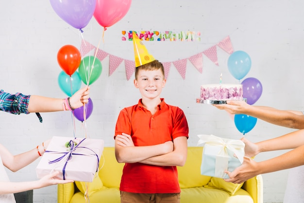 Menino de pé entre a mão do amigo segurando o bolo de aniversário; presentes e balões