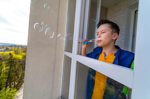 Menino de pé na varanda com bolhas. adolescente se divertindo. conceito de isolamento. pandemia no mundo.