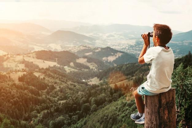 Menino de pé no tronco nas montanhas de verão ao pôr do sol e apreciando a vista da natureza