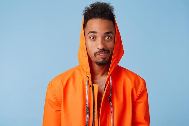 Menino de pele escura afro-americano bonito infeliz usa uma capa de chuva laranja, confuso, angustiado com o mau tempo e planos estragados de fim de semana. parece.
