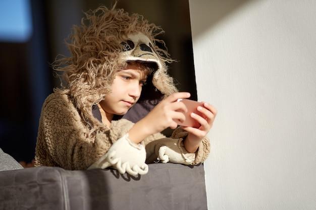 Menino de pijama de preguiça, tocando o telefone móvel