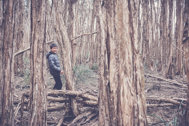 Menino de raça mista feliz asiático tween sorrindo e explorando na floresta