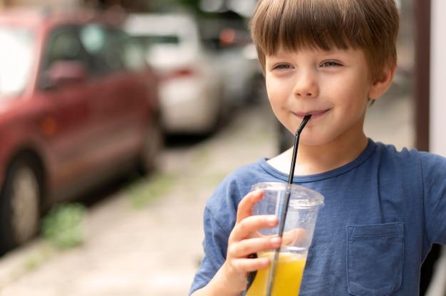 Menino de retrato bebendo suco