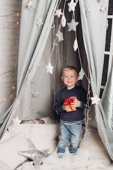 Menino de retrato mostra caixas de natal com presentes