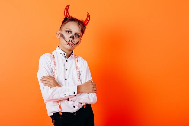 Menino de retrato na maquiagem de disfarce de diabo dobrado as mãos e halloween