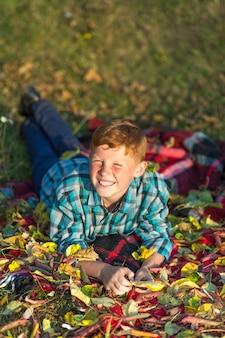 Menino de ruiva sorridente sentado sobre um cobertor de piquenique