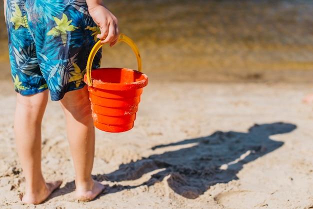 Menino de short segurando balde de brinquedo na praia do mar