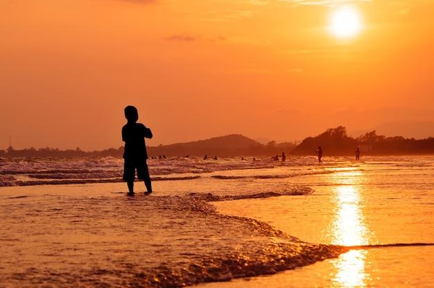 Menino de silhueta em pé na praia ao pôr do sol