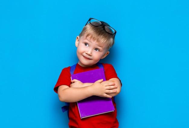 Menino de sorriso feliz pequeno com vidros em sua cabeça, livro nas mãos, schoolbag em seus ombros. de volta à escola. pronto para a escola