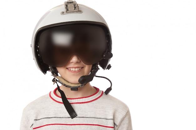 Menino de sorriso novo no capacete piloto isolado no branco.