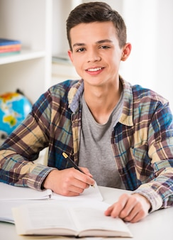 Menino de sorriso novo que senta-se na tabela e que faz trabalhos de casa.