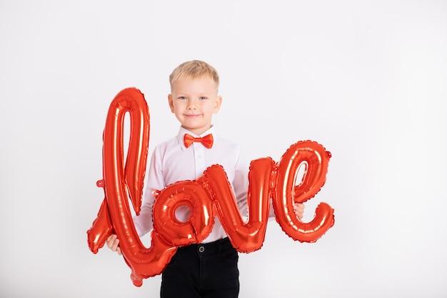 Menino de terno e gravata borboleta vermelha mantém o amor de inscrição de balões em uma parede branca.
