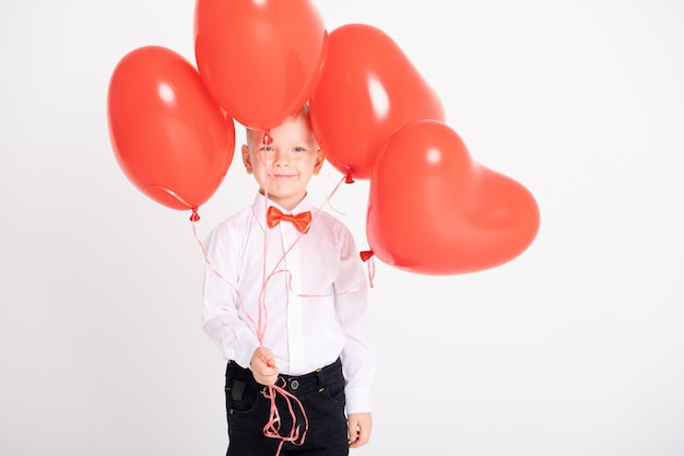 Menino de terno e gravata borboleta vermelha segurando balões em forma de coração