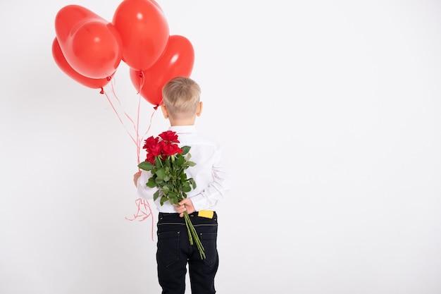 Menino de terno segura buquê de rosas e balões de coração, fica de costas contra uma parede branca.