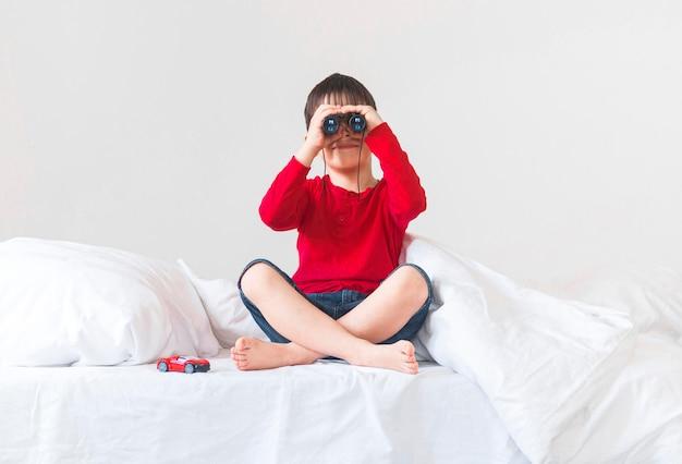 Menino de tiro completo com binóculo na cama