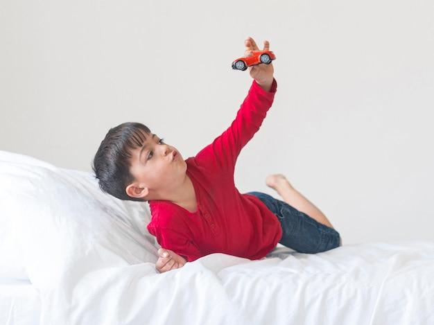 Menino de tiro completo com brinquedo na cama