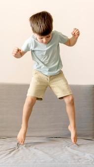Menino de tiro completo pulando no sofá