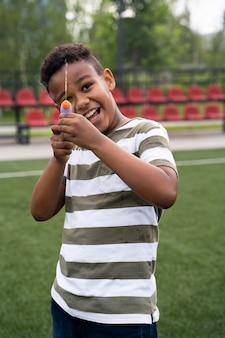 Menino de tiro médio brincando com pistola d'água
