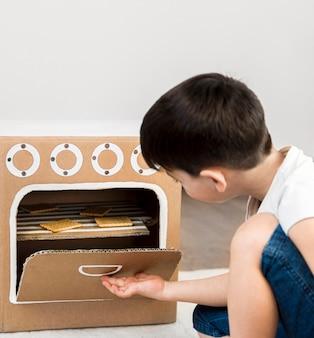 Menino de tiro médio, cozinhando em casa