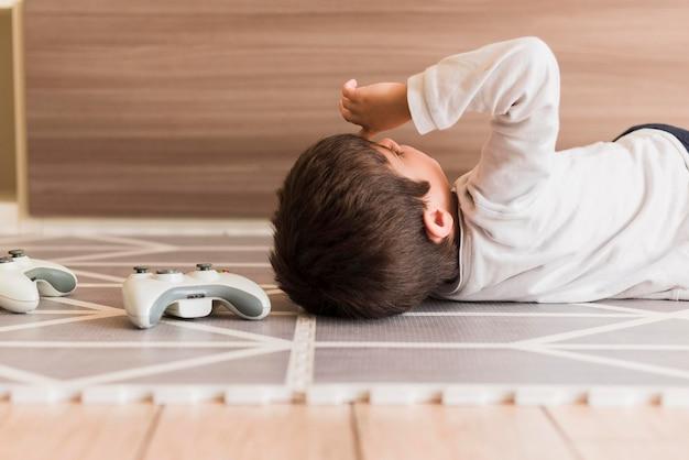 Menino de tiro médio, deitado no chão