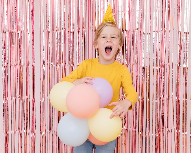 Menino de tiro médio segurando balões coloridos