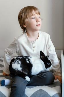 Menino de tiro médio segurando coelho
