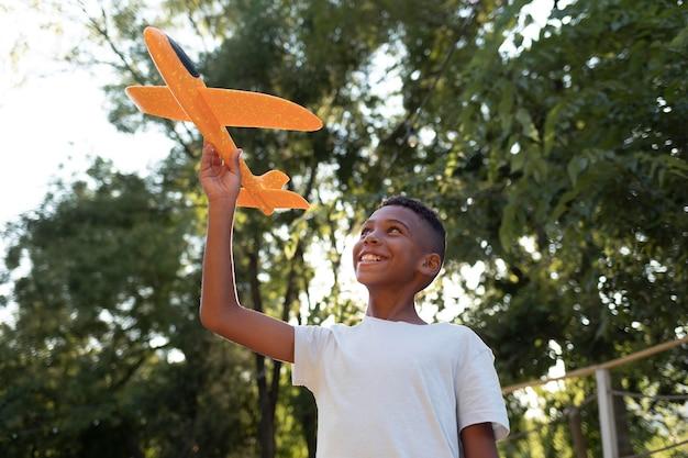 Menino de tiro médio segurando um avião laranja