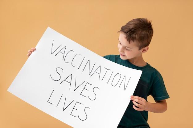 Menino de tiro médio segurando um cartaz com uma mensagem