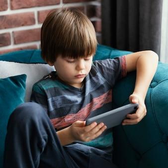Menino de tiro médio segurando um smartphone
