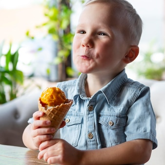 Menino de tiro médio tomando sorvete