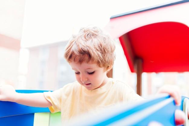 Menino de três anos brincando no balanço de madeira em um parque
